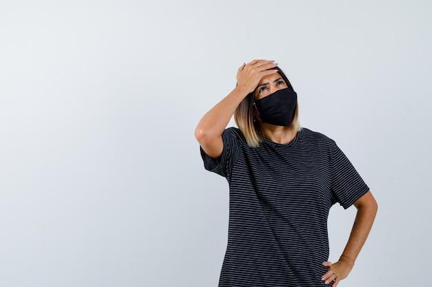 Mulher jovem de vestido preto, máscara preta segurando uma mão na testa e a outra na cintura, olhando para cima e olhando pensativa, vista frontal.