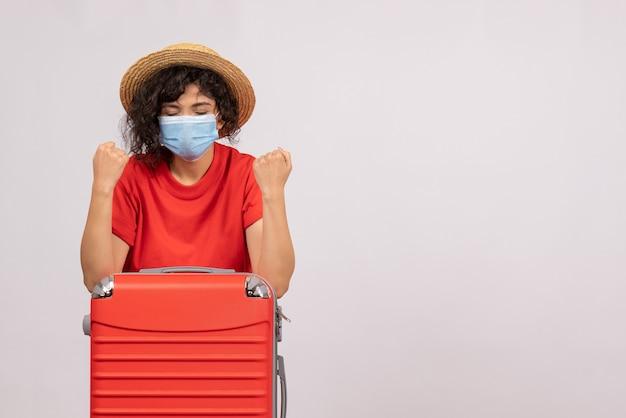 Mulher jovem de vista frontal com bolsa na máscara em cor de fundo branco covid- pandemia viagem sol turista vírus
