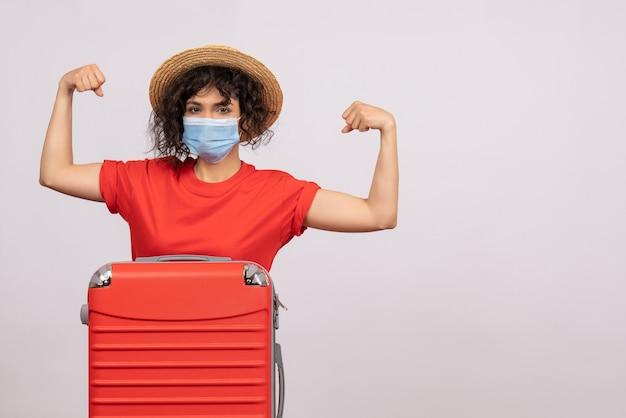 Mulher jovem de vista frontal com bolsa na máscara flexionando sobre fundo branco cor covid- voyage turista férias pandemia de vírus solar