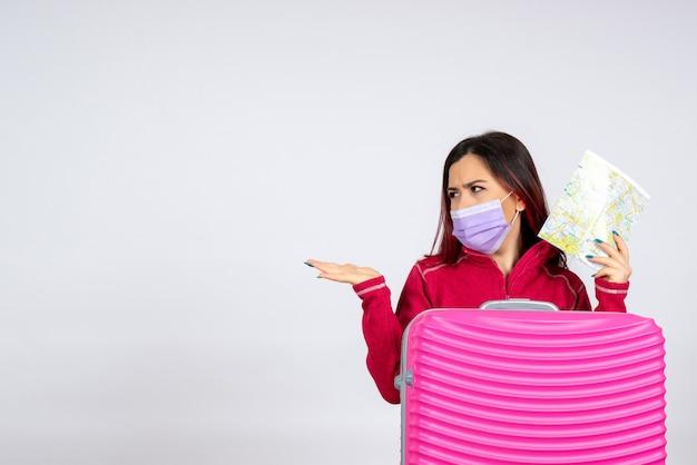 Mulher jovem de vista frontal com bolsa rosa na máscara segurando o mapa na parede branca vírus pandemia viagem mulher covid-