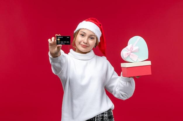Mulher jovem de vista frontal com cartão do banco e presentes em um fundo vermelho