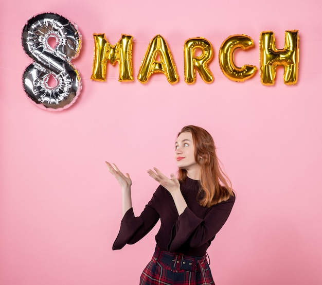 Mulher jovem de vista frontal com decoração de marcha em fundo rosa presente igualdade mulher paixão presente cor do dia da mulher sensual