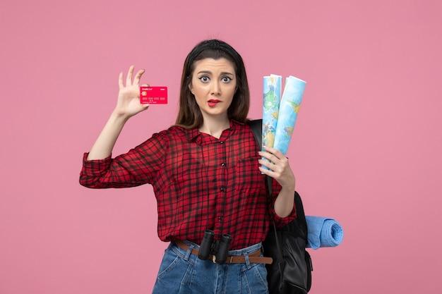 Mulher jovem de vista frontal com mapas e cartão do banco na mesa rosa mulher humana