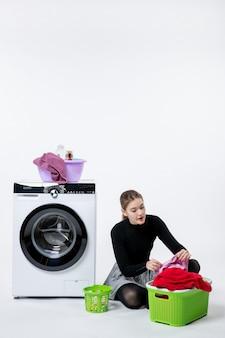 Mulher jovem de vista frontal com máquina de lavar e roupas sujas na parede branca