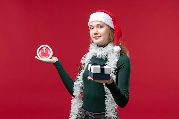 Mulher jovem de vista frontal com presentes com relógio sobre fundo vermelho