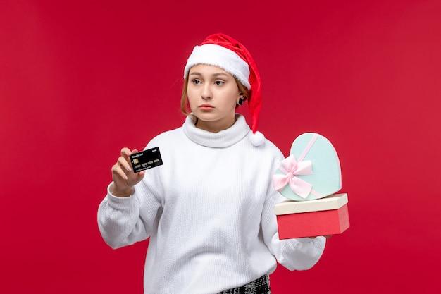 Mulher jovem de vista frontal com presentes e cartão do banco em fundo vermelho