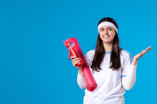 Mulher jovem de vista frontal com tapete para exercícios e garrafa de água na parede azul