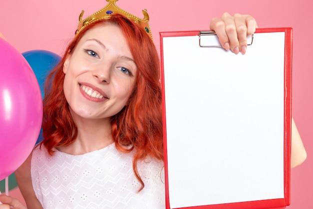 Mulher jovem de vista frontal de perto segurando balões coloridos e uma nota de arquivo na rosa