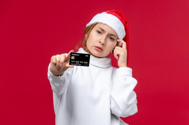 Mulher jovem de vista frontal posando com cartão do banco em fundo vermelho