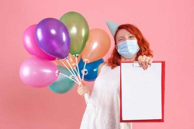 Mulher jovem de vista frontal segurando balões coloridos e nota de arquivo na máscara rosa