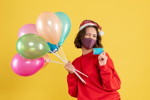 Mulher jovem de vista frontal segurando balões e cartão do banco na máscara em amarelo