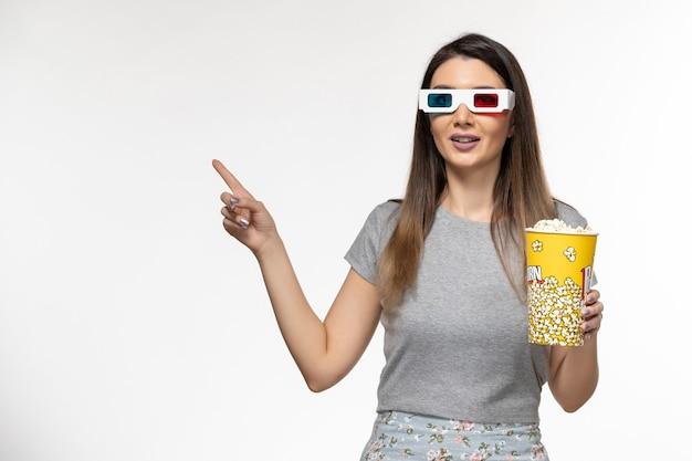 Mulher jovem de vista frontal segurando pipoca e assistindo filme em óculos de sol d na superfície branca clara