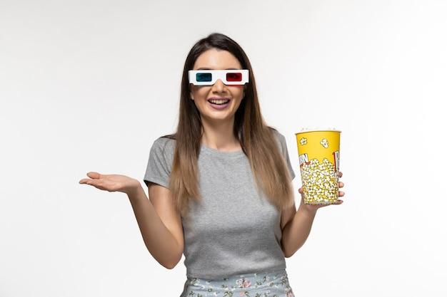 Mulher jovem de vista frontal segurando pipoca e assistindo filme em óculos de sol d na superfície branca