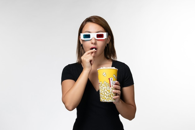 Mulher jovem de vista frontal segurando pipoca e comendo óculos de sol d assistindo filme na superfície branca