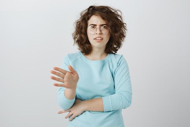 Mulher jovem decepcionada e chateada balançando a cabeça em negação, rejeitar ou proibir algo, dizendo não
