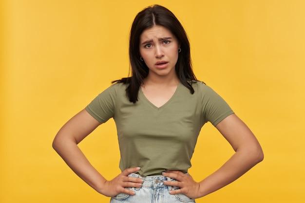 Mulher jovem decepcionada e chateada com cabelo escuro e roupas casuais mantém as mãos na cintura e parece irritada com a parede amarela