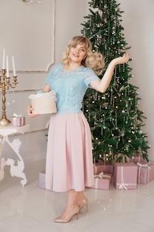 Mulher jovem decora a árvore de natal com brinquedos de natal