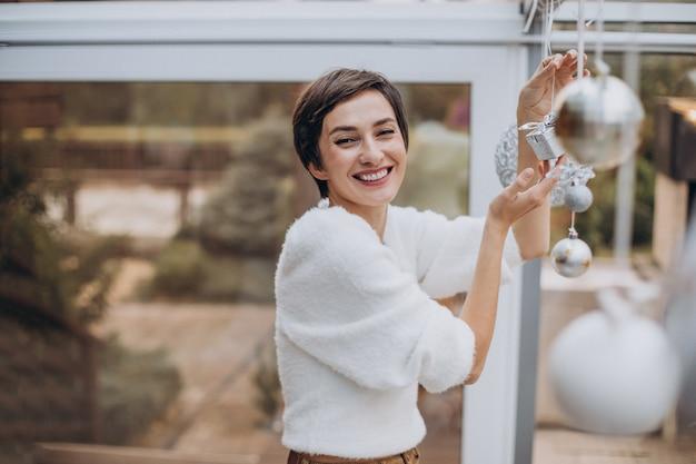 Mulher jovem decorando a casa com brinquedos de natal