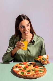 Mulher jovem degustando uma pizza deliciosa