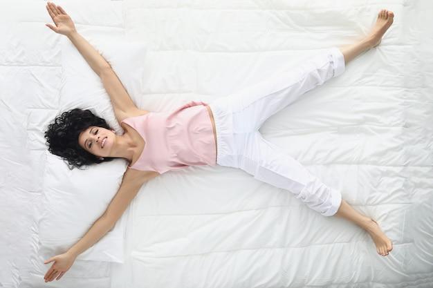Mulher jovem deitada com os braços e as pernas afastados na vista de cima da cama branca