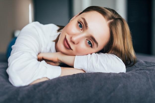 Mulher jovem deitada com uma colcha sobre ela enquanto olha para frente e uma mão em sua bochecha