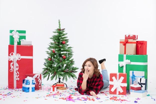 Mulher jovem deitada de frente para os presentes de natal e a árvore do feriado no fundo branco.