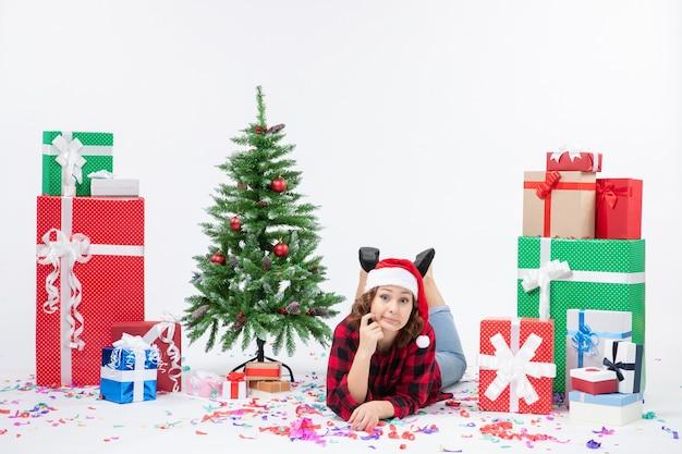 Mulher jovem deitada de frente para os presentes de natal e uma pequena árvore de férias no fundo branco ano novo frio mulher natal neve