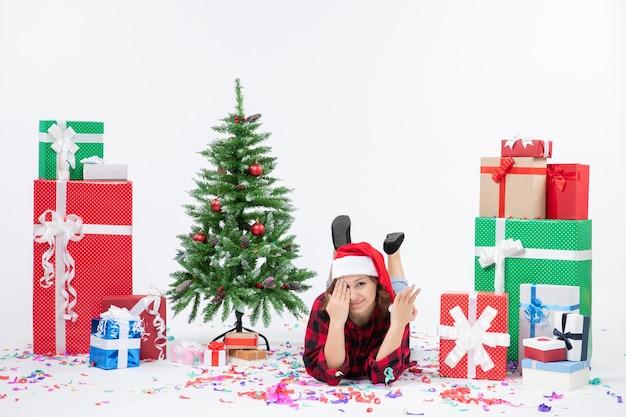 Mulher jovem deitada de frente para os presentes de natal e uma pequena árvore de férias no fundo branco.