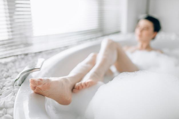 Mulher jovem deitada na banheira com espuma e relaxamento da vista borrada em um banheiro luxuoso com decoração de pedra