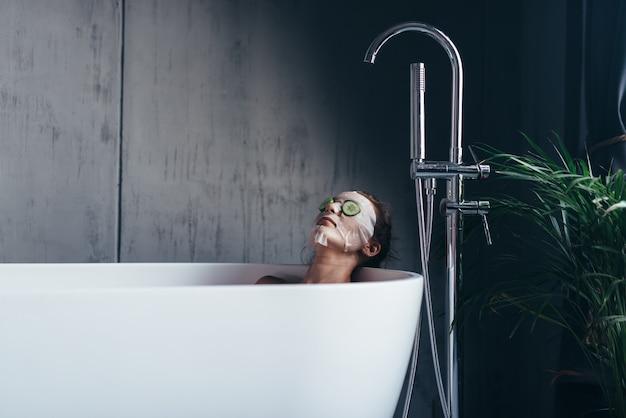 Mulher jovem deitada na banheira com uma máscara e pepinos no rosto