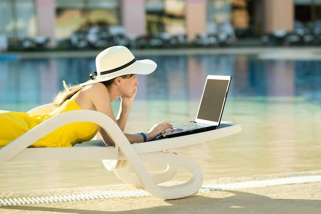 Mulher jovem deitada na cadeira de praia, trabalhando em um computador laptop conectado à internet sem fio, digitando texto nas teclas em um resort de verão