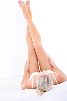 Mulher jovem deitada na cama e acariciando suas pernas perfeitas