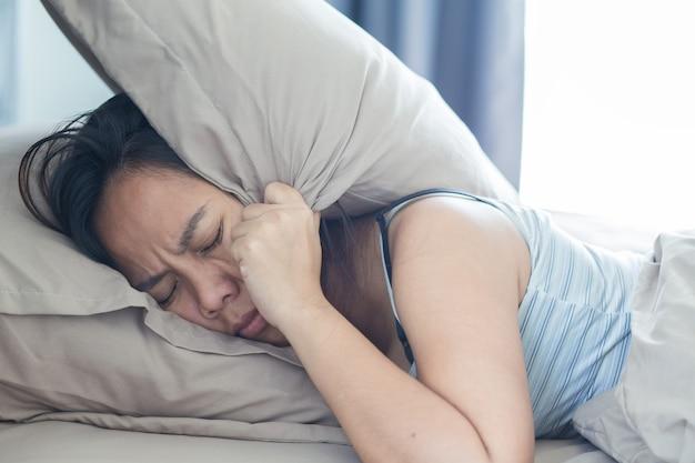 Mulher jovem deitada na cama sofrendo de um som que cobre a cabeça e as orelhas com o travesseiro