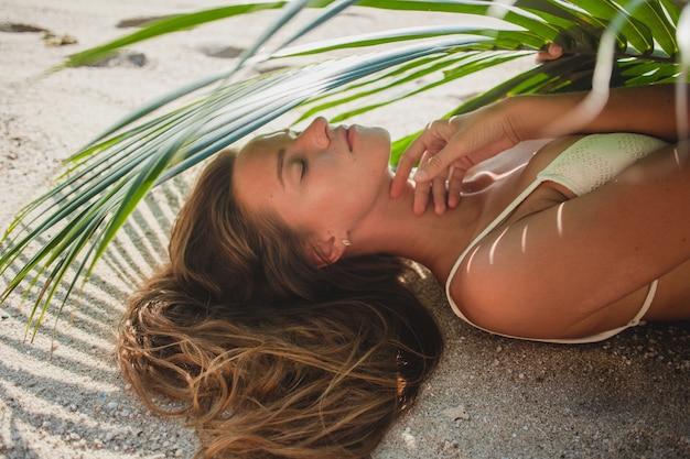 Mulher jovem deitada na praia de areia sob uma folha de palmeira