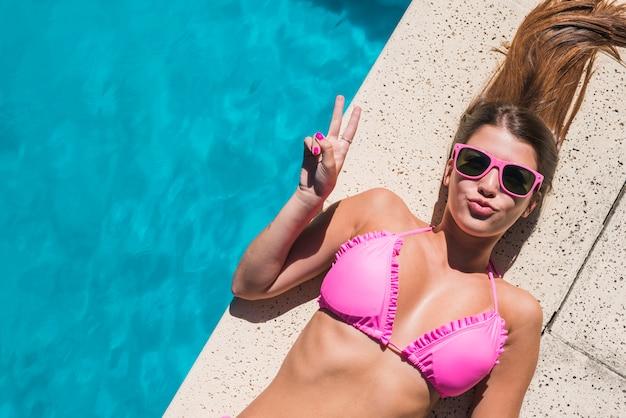 Mulher jovem, deitando, por, piscina, e, mostrando, gesto paz