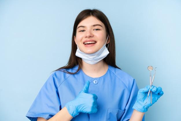 Mulher jovem dentista segurando ferramentas sobre parede azul isolada, dando um polegar para cima gesto