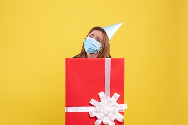 Mulher jovem dentro da caixa de presente com máscara esterilizada triste