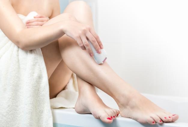 Mulher jovem depilando pernas depois de tomar banho