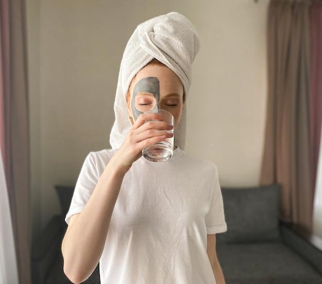 Mulher jovem depois do banho com uma toalha na cabeça e uma máscara de argila no rosto bebe água