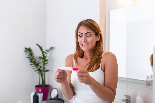 Mulher jovem deprimida com sentimentos de ansiedade, segurando o teste de gravidez negativo no banheiro.
