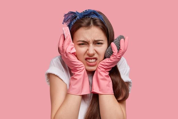 Mulher jovem deprimida e ocupada mantém as mãos perto das bochechas, carrega esponjas, olha para o quarto bagunçado, tem que arrumar tudo
