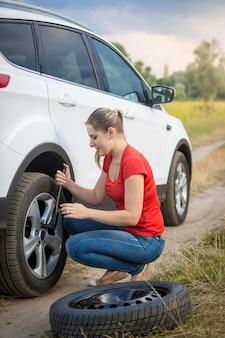 Mulher jovem desaparafusando as porcas da roda plana do carro no campo