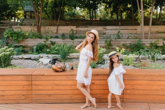 Mulher jovem descalça e menina em pé, costas com costas na frente do canteiro de flores. retrato de corpo inteiro ao ar livre da elegante mãe e filha, vestindo roupas semelhantes no parque de verão.