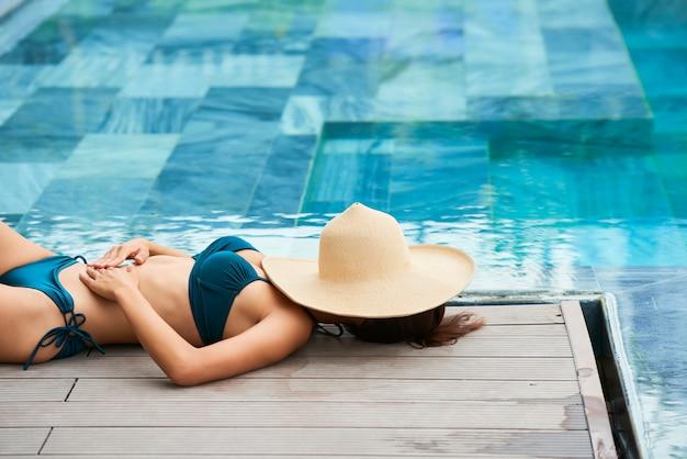 Mulher jovem descansando à beira da piscina