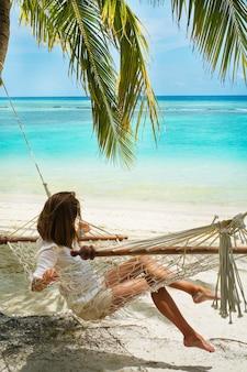 Mulher jovem descansando em uma rede na margem e olhando para o oceano