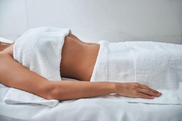 Mulher jovem descansando na mesa de massagem em salão de spa