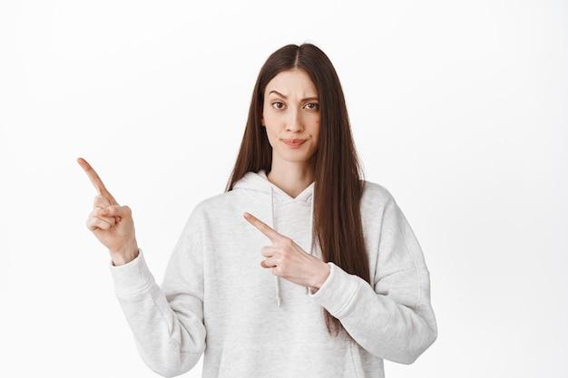 Mulher jovem desconfiada e duvidosa apontando para o canto superior esquerdo, olhando com dúvida e descrença, erguer a sobrancelha, mostrando algo estranho à parte, em pé sobre uma parede branca