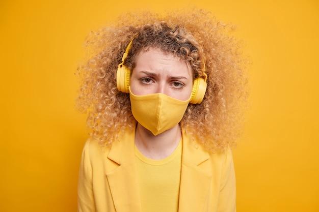 Mulher jovem descontente e desapontada usa máscara protetora e sente-se solitária ficando em casa sozinha com auto-isolamento ouve música através de poses de fones de ouvido estéreo sem fio contra a parede amarela