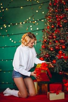 Mulher jovem desembalar presentes por árvore de natal