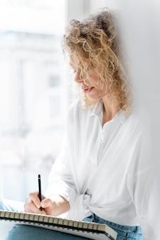 Mulher jovem desenhando em casa perto da janela